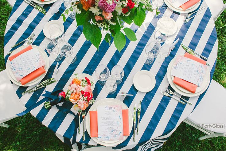 Colorful table setting. White and navy blue striped tablecloth and corall napkins.
