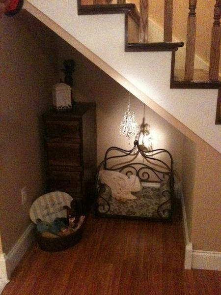 This under-the-stairs dog room -- complete with chandelier! perfect for my girls :)