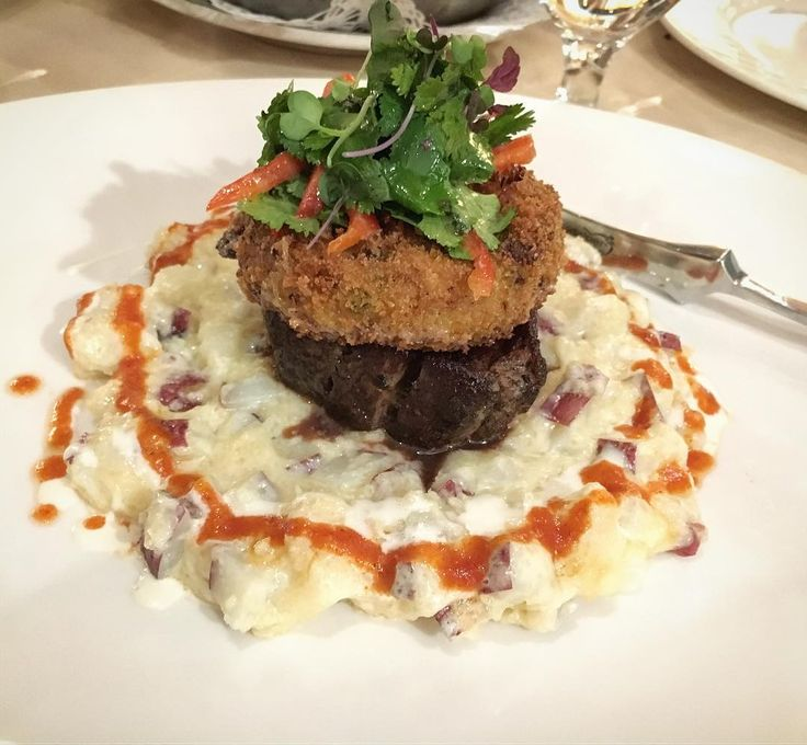 Spanish Tavern | filet mignon topped with a crab cake and fresh salad sitting on a cheesy potato mix