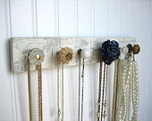 knobs. Pick out your favorite knobs, paint you a strip of wood in the color of your choice , screw the knobs in and you have a custom neck less holder. Can be shabby chic or elegant. Your choice