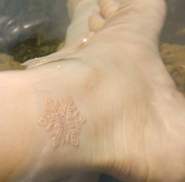 Freshly inked white ink snowflake on ankle via Rosa Maria Alejandra