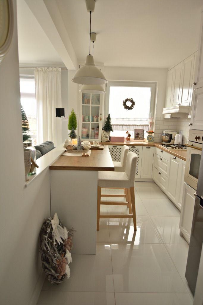 Białe szafki i biała podłoga w wąskiej kuchni
