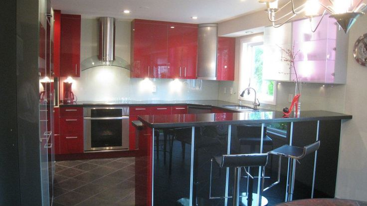 These clients wanted a bold kitchen. 7J Design added red cupboards and storage for this dramatic space.