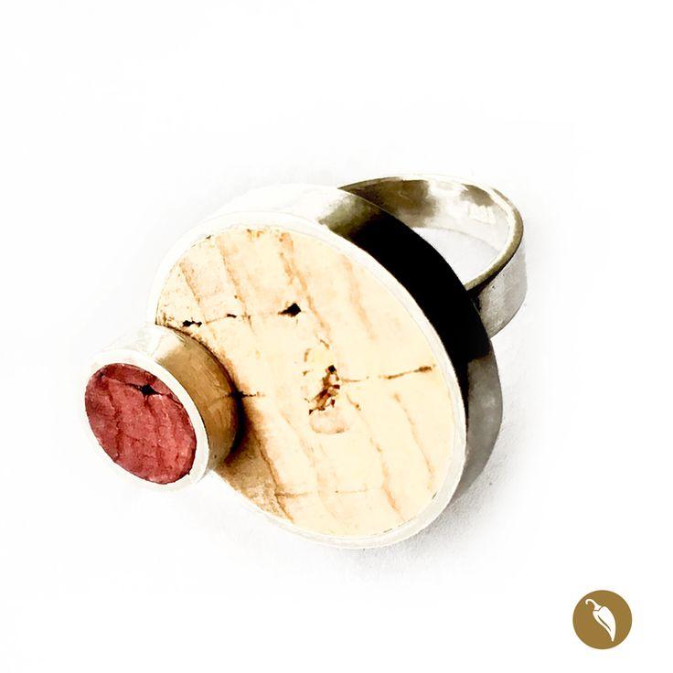 Anillo de plata con dos círculos de plata, uno sobre otro, que enmarcan pequeñas piezas de corcho reciclado. Una de color natural y otra teñida por el contacto con el vino tinto. Weichafe recicla los corchos de botellas de vino que fueron vaciadas y los integra a su joyería como huella de un momento inolvidable. La autora rescata el corcho por tratarse de un insumo que cumple un doble propósito: reciclar y hablar de identidad. Reciclaje, porque son corchos reutilizados e identidad porque…