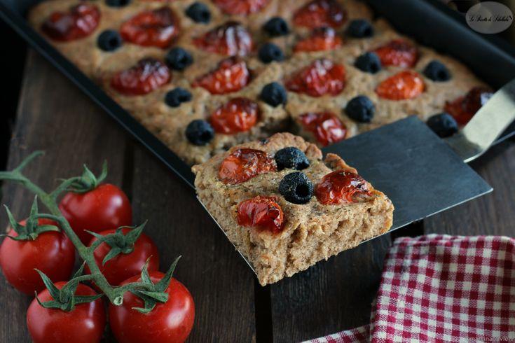 Ricetta della focaccia integrale con pomodorini e olive. Soffice e profumata, è ideale per accompagnare formaggi e salumi.