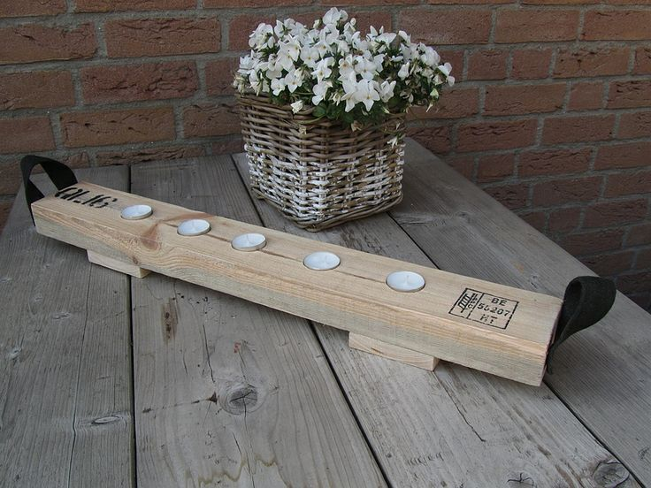 tealight holder made from a bar of a pallet, canvas straps on the side.