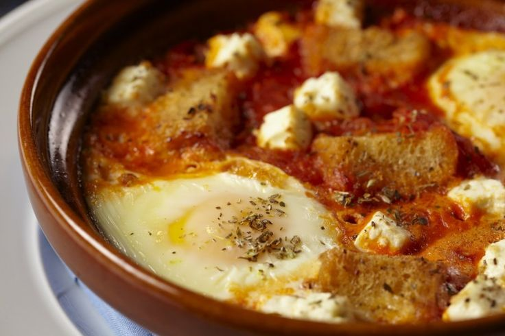 Greek eggs with tomato:  8 free-range eggs, 3 tablespoons extra-virgin olive oil, 2 cloves garlic, peeled and sliced,1/4 teaspoon dried Greek oregano,1 cup tomatoes, peeled, seeded and chopped  16 ounces tomato sauce