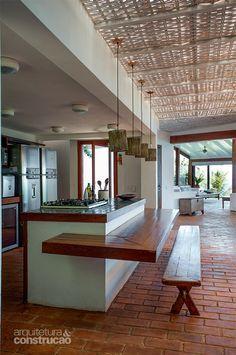 Sob a telha de fibra de vidro, a trama de palha deixa entrar luz filtrada na cozinha. Projeto Vázquez + Junqueira Arquitetos Associados.