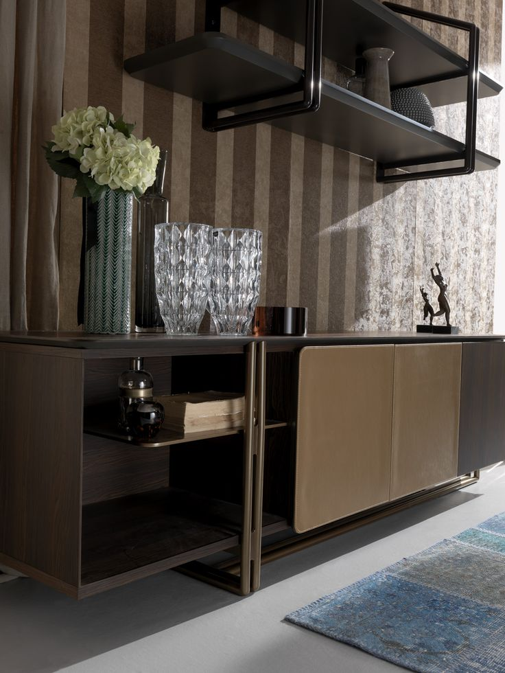 This refined and sophisticated console has an exclusive design. With leather covered doors and an open compartment divided by a metal shelf that gives an overlapping effect. It has a tubular structure that embraces the shelf and then blends in with the surface. Perfect for private spaces. A classic piece, with attention to detail, this console is ideal for professional or prestigious offices.