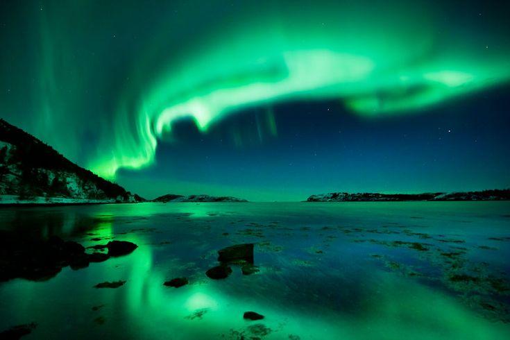 A green aurora swirls across the night sky in Nord-Trøndelag, Norway