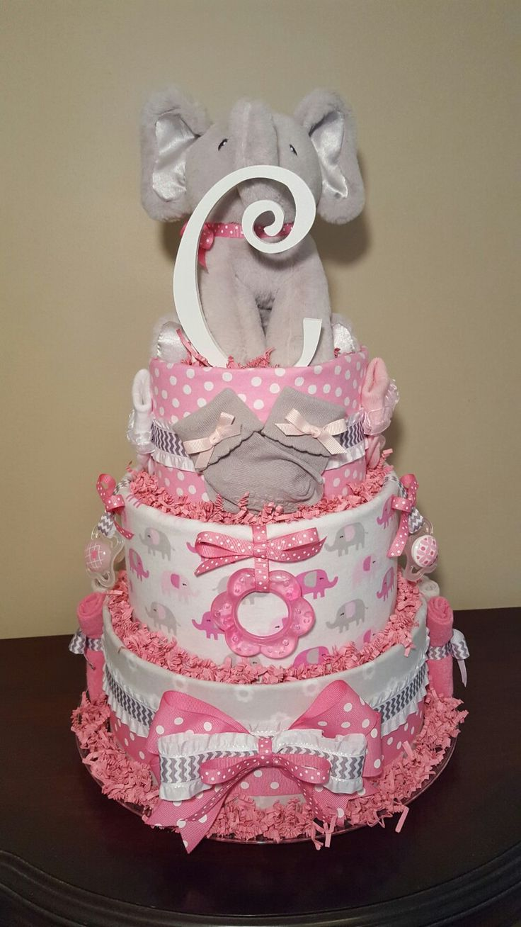 Adorable! Pink and gray elephant diaper cake, baby shower centerpiece gift loaded with 4 Carter's receiving blankets, 6 washcloths,  3 pair of Carter's  socks, 2 MAM pacifiers,  1 teether, Gund musical elephant and the initial letter of your choice. 68 pampers swaddlers.  Visit my Facebook page Simply Showers for more pics and orders.