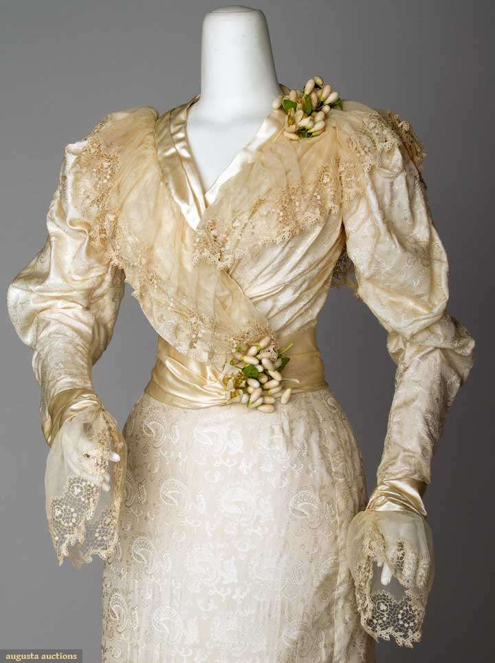 SILK WEDDING GOWN, PHILA., 1890s Cream silk damask in paisley pattern, trained skirt attached to bodice at CB, lace & self fabric bow trims, Eembroidered net lace collar & cuffs, wax orange blossom clusters at shoulder & waist. Detaile front