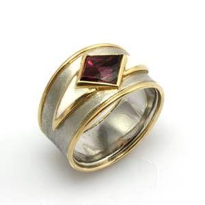 Der Ring ist mit einem rautenförmigen Rhodolith (1,99 ct) gearbeitet. Der Rhodolith gehört zur Granat-Gruppe und zeichnet sich durch seine hohe Lichtbrechung sowie seinen besonders schönen, transparenten Rotton aus. Seitlich des Steines ist jeweils ein spitz zulaufendes Segment mit weißem Colorit aufgetragen. Die Ringschiene ist aus Platin und 750er Gold gearbeitet. Der Ring ist von Meisterhand gefertigt und ein Unikat.  Stempelung Platin + 750er Gold, Meisterstempel sowie Münchner Kindl