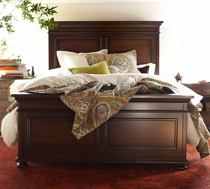 This paisley bedding and a dark wood bed frame bring