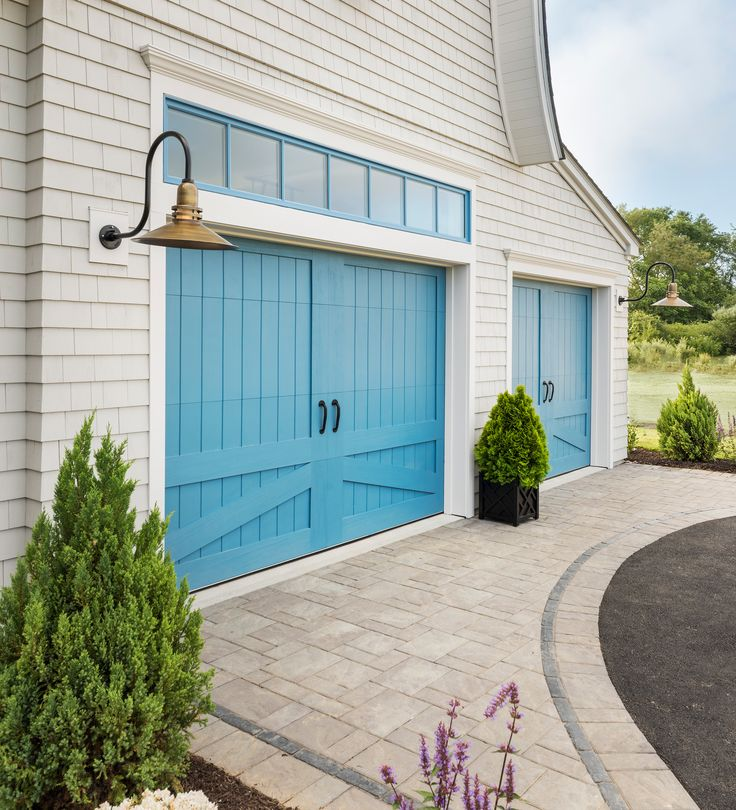 Watercolor Blue faux wood carriage house garage doors by Clopay and two-tone pavers by Unilock make a grand statement.