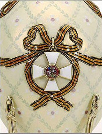 """Su una di tali medaglie è raffigurata la croce dell'Ordine di San Giorgio in smalto bianco e rosso; aprendola rivela un ritratto in miniatura dello Zar Nicola II.  Sull'altro lato dell'uovo una medaglia di San Giorgio d'argento reca il profilo di Nicola II, sul bordo è scritto in cirillico """"Sua Maestà Nicola II, autocrate di tutte le Russie"""". Si apre per rivelare un ritratto in miniatura dello Zarevič Aleksej; sul rovescio della medaglia è inscritto in cirillico, """"Per coraggio, IV classe""""."""