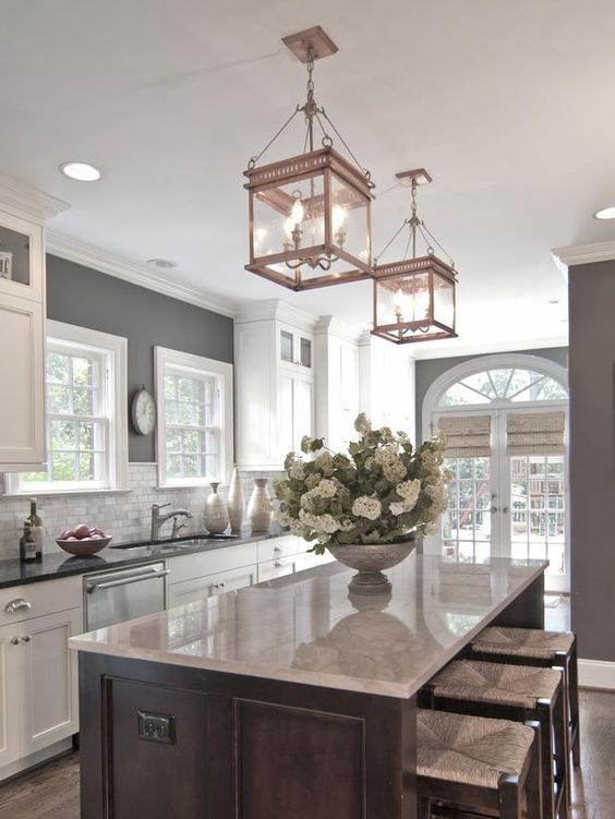 White cabinets, grey walls, neutral backslash, dark island--design by  Carolina