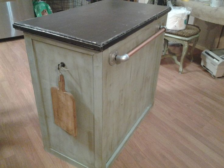 Yard sale find. Very ugly homemade cabinet transformed into center island. Chalk painted in Duck egg blue and black top with distressing and dark wax .  Towel holder from copper pipe and galvanized hardware.