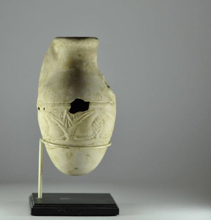 Assyrian faience vessel, 9th-7th century B.C. Assyrian faience vessel, Mesopotamian Levantine faience vessel molded with flowers and leaves, egyptianizing, spout missing and holes in sides, 15 cm high. Private collection