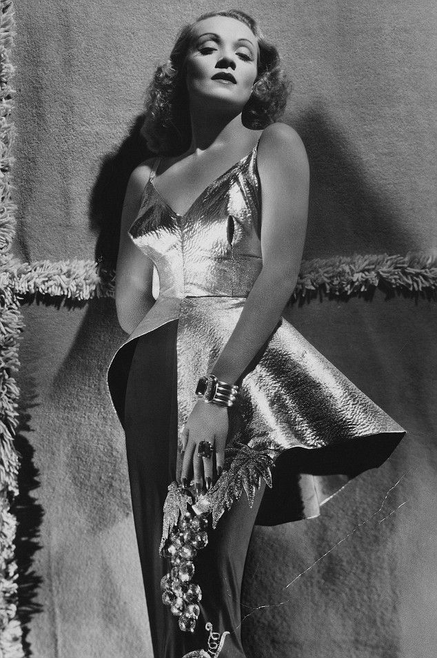 Marlene Dietrich poses in a stiffened gold lamé dress, 1940