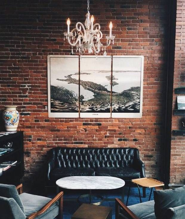 exposed brick, leather sofa, chandelier