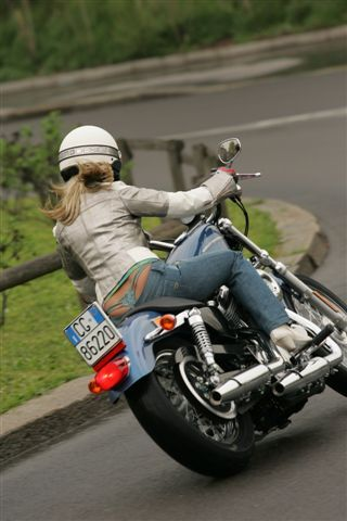 Perfect illustration of the dynamics of turning on a two-wheeled vehicle -- leaning into the turn, so that gravity can balance out the centrifugal force of the turn, and front wheel essentially straight. I also commend the rider for wearing a helmet, and for riding with her arms and legs covered.