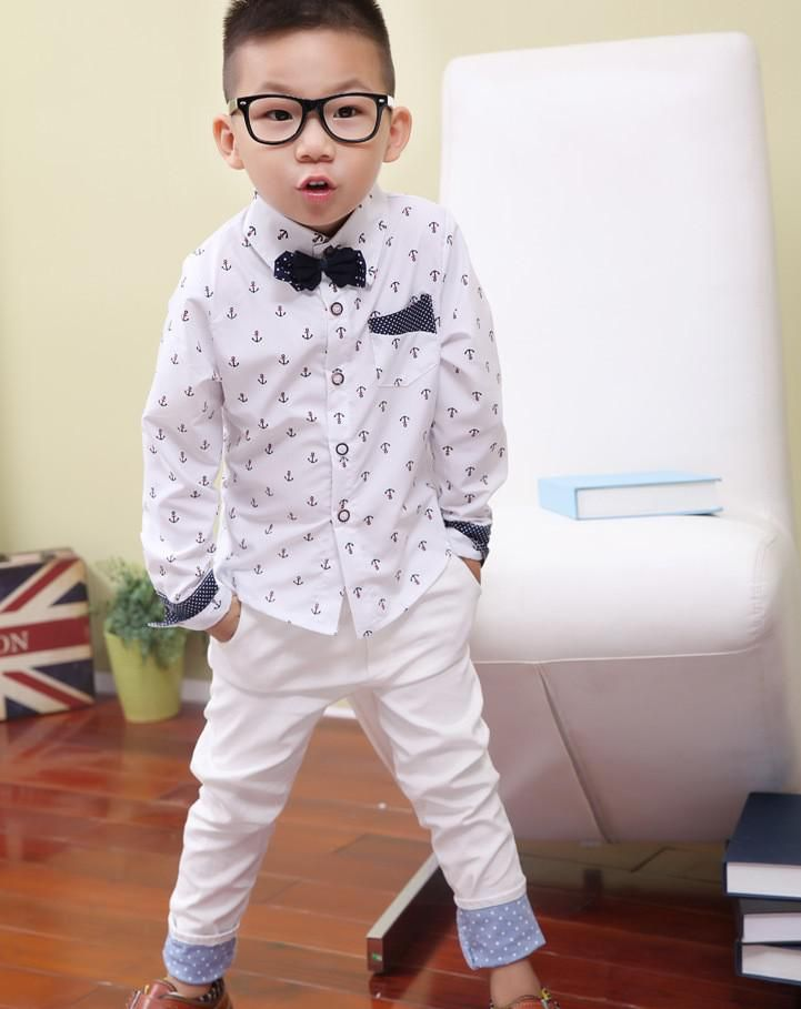White dress shirt with anchor pattern, front pocket and detachable bow tie. Navy with white polka dot detail inside the collar lining, on the front pocket and sleeve cuffs. Looks great with our white pants. Sizes 2-7y. $27. Visit us at babylunaboutique.com