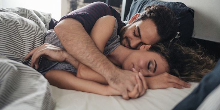 Young Caucasian couple sleeping in a king-size bed. | The Position You Cuddle In Says Everything About Your Relationship