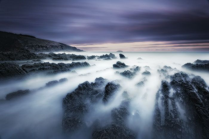 Long exposure creates a dreamy surreal effect on the oceans water as the clouds streak through the sky above off Emerald Beach - New South Wales, Australia.