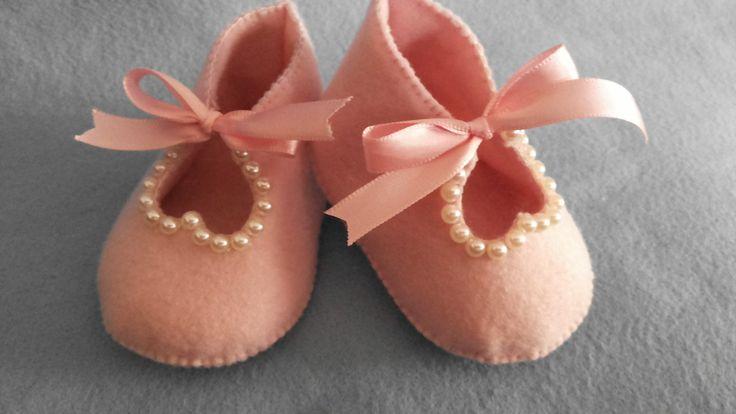 Sapatinho de feltro com aplicação de meias pérolas totalmente feito a mão. Usado comumente como lembrancinha de nascimento. Pode-se colocar guloseimas dentro. Pode ser feito como chaveiro também.