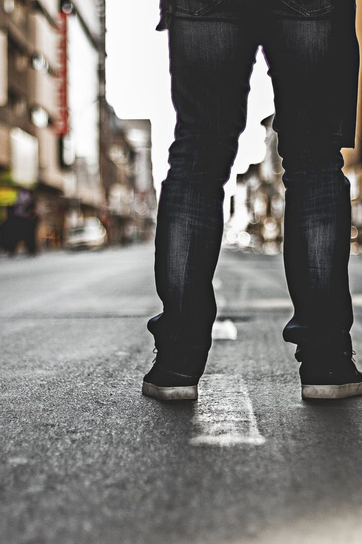 Man in Black Denim Jeans Standing on Grey Concrete Road