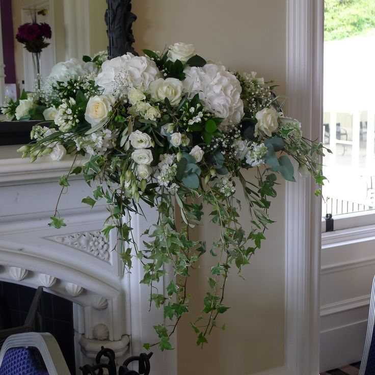 An arrangement made for a fireplace in a hotel made up of beautiful white hydrangea, white avalanche rose, white eustoma with trails of ivy and cinerea eucalyptus