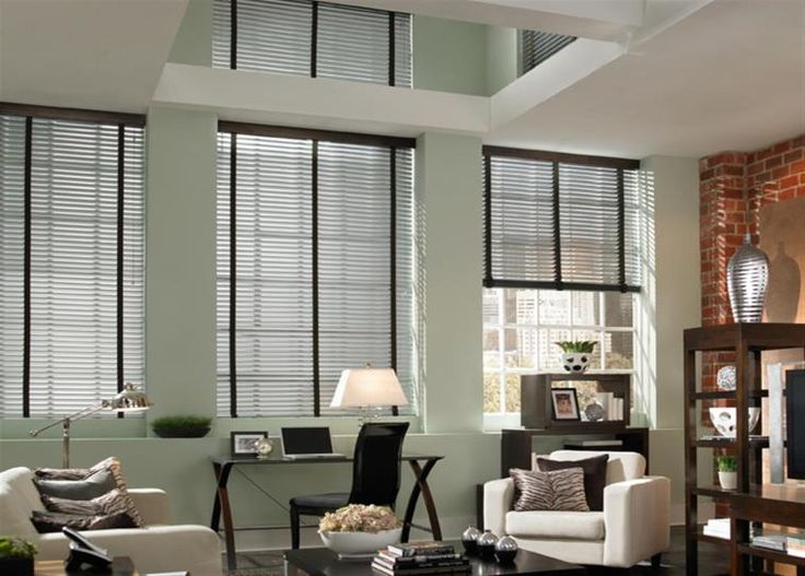 Brushed aluminum blinds, pictured here with chocolate tapes, complement the existing décor of this living room. #BudgetBlinds