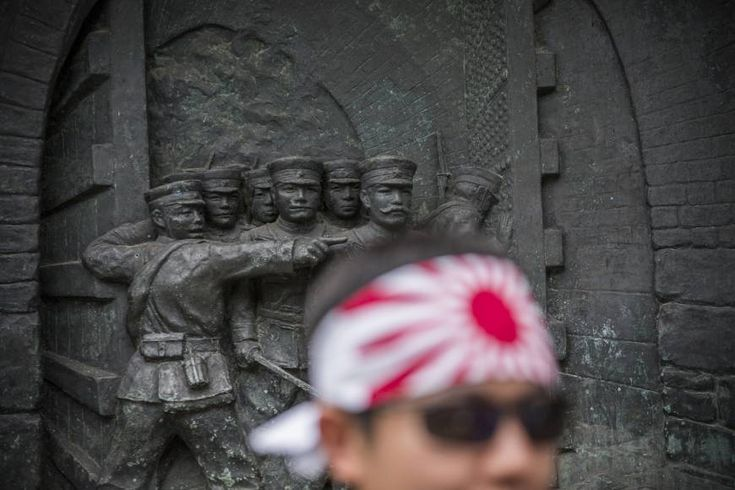 Punitive measures: A man wearing the Rising Sun flag as a head band visits war-linked Yasukuni Shrine in Tokyo, a symbol of Japan's past militarism. Tokyo has avoided paying the $37 million it owes UNESCO, partly due to the organization's decision last year to include a Chinese submission on