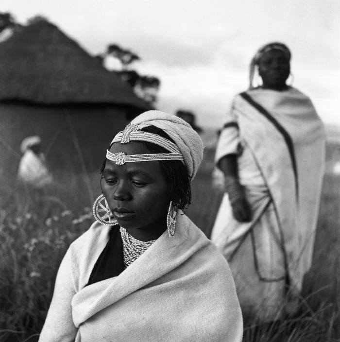 Africa | The Pondo tribe girls have special types of beadwork headdresses which denote their status in life. Adolescent girls wear a single band round the forehead, betrothed girls a double band, and married women yet more varied designs. The married women also change their blanket of red ochre for one of pale blue after they have been proved good and faithful wives. |  Image and caption © George Rodger, 1948.
