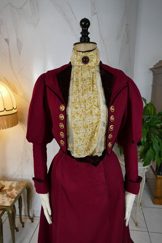 Three-piece walking or promenade dress, circa 1899-1900. The dress consists of blouse / underpants, skirt and bolero. The ensemble is made of red wool and decorated with red velvet. The blouse is worked in the form of an insert, in the chest area beautifully decorated with folded