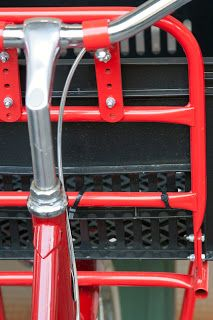 Steering wheel of a red bike with basket, Asmterdam.