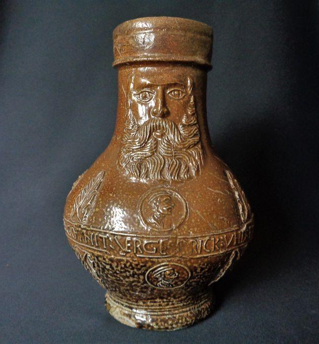 Middeleeuwse steengoed baardmankruik met decoraties en tekstband ERGE DRICK:UND:ES:GOTNIT: Datering - 16e eeuw, 1525 - 1575. Herkomst - Duitsland/Frechen. hoog 187 mm