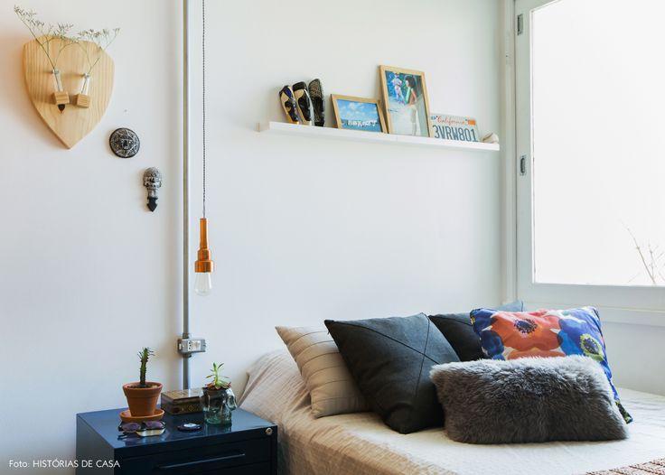 Quarto masculino tem almofada estampada, quadros, máscaras e objetos de decoração na parede.