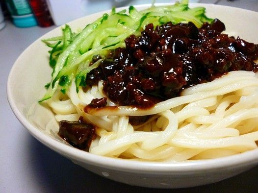 Zhajiangmian, or 炸酱面 in Chinese, originated in Beijing, is a Chinese noodle dish consisting of thick wheat noodles topped with a mixture of ground pork, cucumber and stir-fried with fermented soybean paste.