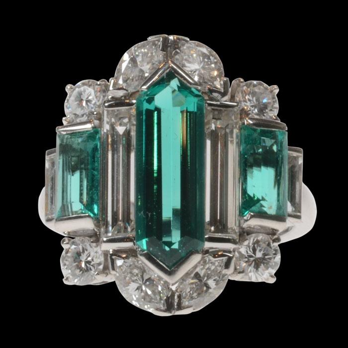 Anillo de cóctel inusual del panel central engastado con una esmeralda hexagonal alargada y otras dos esmeraldas paso de corte destacadas por baguette, brillante y diamantes marquesa Art Deco circa 1930