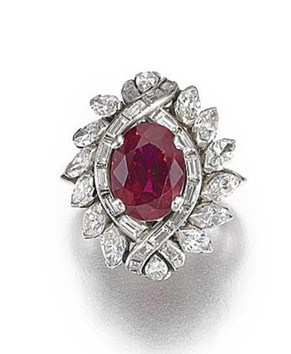 RUBY AND DIAMOND RING.  Set to the centre with an oval ruby framed by marquise-shaped and baguette diamonds