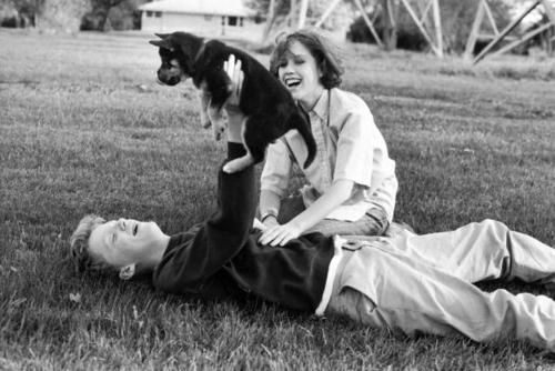 Anthony Michael Hall and Molly Ringwald playing with a puppy on location shooting the Breakfast Club