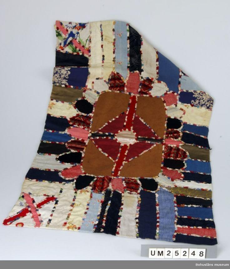 """Lapptäcksmatta,1920-1925.Sverige, Bohuslän, Sotenäs. Tillverkad av Charlotte i Svenserud till en grannfamilj. På undersidan av grov säckväv i jute finns stämpeln """"W. Weibull, spec rotfruktsfröer. Landskrona. På framsidan lapptäcksmönster av bitar av bomullstyg, konstfiber samt stickat mönster, trol. från en tröja. Bitarna fastsydda i mönster, i mitten liksidigt kors i rektangel o däromkring tygbitar i olika former. Mellan alla tyger bårder av små tygfragment i olika färger."""