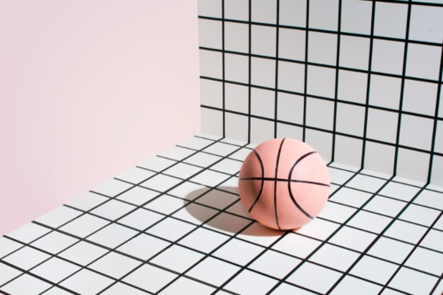 basket ball laying on a black and white grid, next to pastel pink wall. Graphic and geometric, nice work. #graphic #grid #pastel.