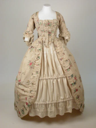 Sack-backed gown, c. 1770, England. Chinese silk painted with flower posies, birds and butterflies on natural ground. Square neckline, closed bodice lined with linen , open skirt and full sack back. Later addition (1770's) of box pleated robings (including across bodice front to give effect of stomacher) and falling fan cuffs, also cord loops to skirt for drawing up into polonaise. National Trust.