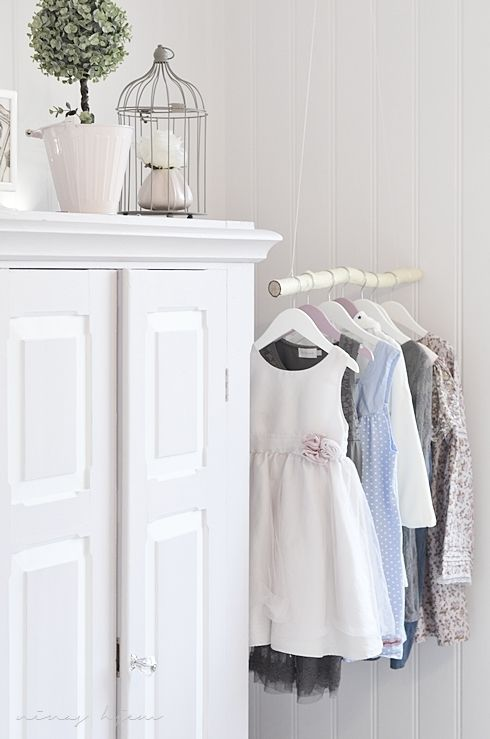 White armoire cupboard with vignette on top, decorative hanging for children's clothes in the nursery