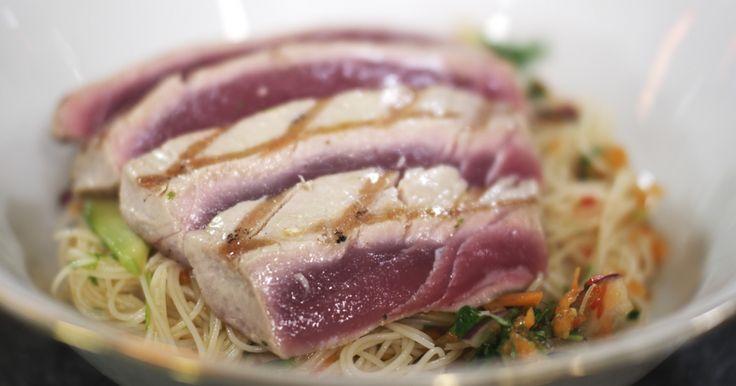 Tonijn is een luxeproduct dat je beslist niet elke dag hoeft te eten. Maar, heel af en toe mag je je eens laten verleiden om zo'n stukje edele vis op de tafel te zetten. Jeroen bereidt de vis het liefst zo puur mogelijk, zodat je volop van de smaak kan genieten. Bij de tonijnsteak hoort een Thais geïnspireerde noedelsla met een pittige dressing en veel verse groene kruiden.extra materiaal:een wokeen groentenraspeen borsteltje of penseeleen grillpan