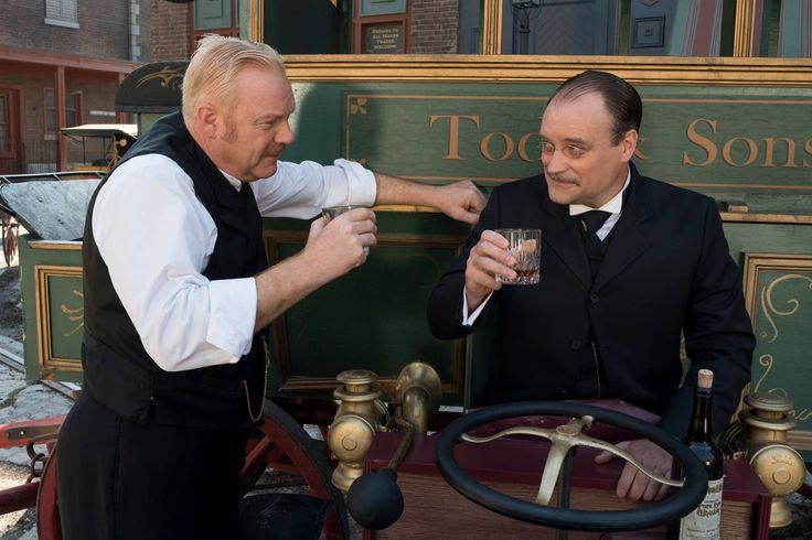 Inspector Brackenreid (Thomas Craig) and Dilton Dilbert (David Hewlett) lift their glasses to enjoy one last drink as friends.