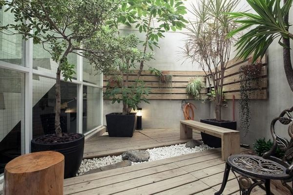 asian inspired small garden wooden deck gravel potted plants wooden garden bench privacy walls